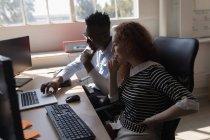 Ejecutivos discutiendo sobre portátil en el escritorio en la oficina - foto de stock