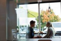 Vue latérale du couple interagissant les uns avec les autres dans le café — Photo de stock