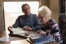 Senior couple looking photo album in living room at home — Stock Photo
