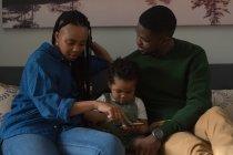 Familia usando teléfono móvil en una sala de estar en casa - foto de stock