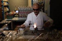 Внимательный работник-мужчина с помощью сварочной горелки на стекольном заводе — стоковое фото