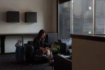 Empresaria con tableta digital en el lobby del hotel - foto de stock