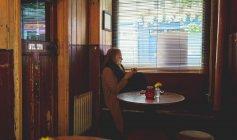 Руда жінці за допомогою мобільного телефону під час за кавою в кафе — стокове фото