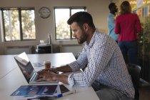 Uomo d'affari utilizzando il computer portatile in ufficio — Foto stock
