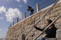 Улыбающаяся женщина делает селфи на лестнице — стоковое фото