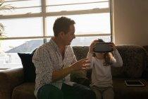 Девочка использует гарнитуру виртуальной реальности с отцом в гостиной дома — стоковое фото