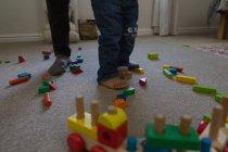 Низкая часть отца и сына, играя в гостиной дома — стоковое фото