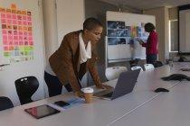 Жіночий бізнес виконавчий дивлячись ноутбука в офісі — стокове фото