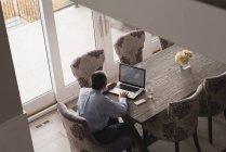 Rückansicht eines älteren Mannes mit Laptop auf Esstisch zu Hause — Stockfoto