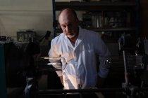 Travailleur masculin attentif examinant le produit en verre dans l'usine — Photo de stock