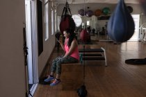 Side view of female boxer using mobile phone in fitness studio — Stock Photo