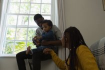 Família usando telefone celular em uma sala de estar em casa — Fotografia de Stock