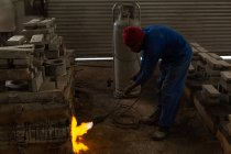 Worker heating furnace with flaming torch in foundry — Stock Photo