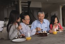 Grandparents and granddaughters having birthday cake at home — Stock Photo