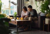 Pareja usando el teléfono móvil mientras tiene comida en el sofá en la sala de estar en casa - foto de stock