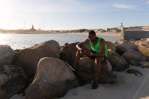 Männliche Sportler mit Handy in Strandnähe an einem sonnigen Tag — Stockfoto