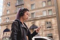 Escuchar música hermosa mujer en el teléfono móvil - foto de stock