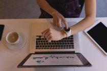 Sección media de la mujer de negocios usando smartwatch en el escritorio en la oficina - foto de stock