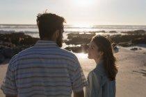 Jeune couple se regardant sur la plage — Photo de stock