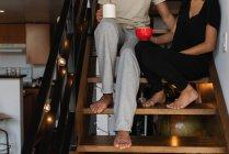 Baixa seção de casal tomando café em escadas em casa — Fotografia de Stock