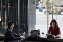 Деловые люди, использующие мобильный телефон и цифровой планшет на стойке бара в отеле — стоковое фото