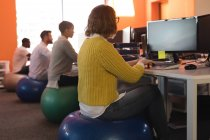 Business executives working at desk while sitting on exercise ball in office — Stock Photo