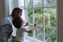 Padre e hijo de pie cerca de la ventana en casa - foto de stock