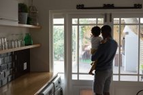 Rear view of father and son looking outside the door from kitchen — Stock Photo