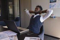 Uomo d'affari seduto con le mani dietro la testa in sala conferenze in ufficio — Foto stock