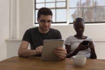 Dirigenti che utilizzano tablet digitale e telefono cellulare in sala conferenze in ufficio — Foto stock