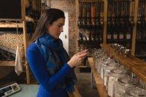 Молода жінка, що використання мобільного телефону у супермаркеті — стокове фото