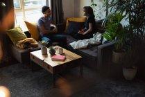 Couple interagissant les uns avec les autres tout en prenant un café sur le canapé dans le salon à la maison — Photo de stock