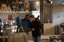 Male workers discussing in foundry workshop — Stock Photo