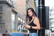 Вдумчивый женщина, используя мобильный телефон в городе — стоковое фото