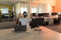 Бизнес-руководитель с помощью гарнитуры виртуальной реальности на рабочем столе в офисе — стоковое фото
