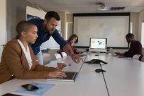 Business Executive discutant sur ordinateur portable dans la salle de conférence au bureau — Photo de stock