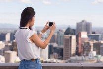 Vista laterale della donna cliccando foto sul cellulare — Foto stock