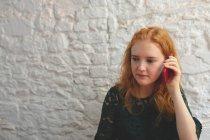 Donna rossa che parla al telefono cellulare nel caffè — Foto stock