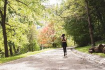 Rear view of female jogger running in the park — Stock Photo