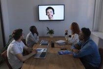 Imprenditori che interagiscono tramite videochiamata in conferenza in ufficio — Foto stock