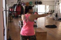 Задний вид женского боксера растяжения с шкивом в фитнес-студии — стоковое фото