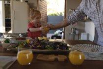 Отец подает апельсиновый сок своей дочери на обеденном столе дома — стоковое фото