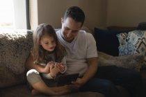 Батько і дочка, використовуючи цифровий планшет на дивані у вітальні на дому — стокове фото