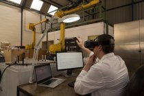 Robotics engineer using virtual reality headset at desk in warehouse — Stock Photo