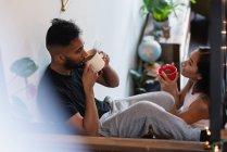Вид сбоку на супружескую пару, пьющую кофе в доме — стоковое фото