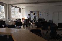 Чоловічий керівників, обговорюючи над наліпок в офісі — стокове фото