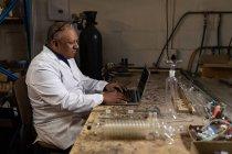 Vista laterale del lavoratore che utilizza il computer portatile in fabbrica di vetro — Foto stock