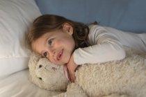 Fille détente avec ours en peluche dans la chambre à coucher à la maison — Photo de stock