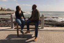 Пара, взаимодействующая друг с другом на набережной у моря — стоковое фото