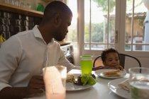 Vater füttert Sohn zu Hause in Küche mit Lebensmitteln — Stockfoto